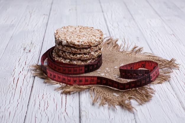 Dieta padaria de arroz e medida de fita vermelha mentira sobre a mesa de madeira branca