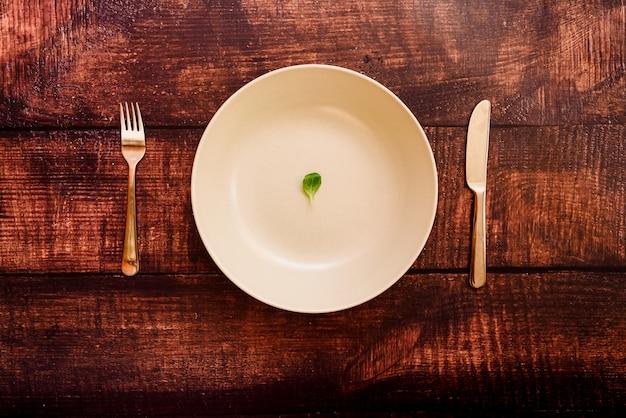 Dieta para perder peso, imagem de prato e talheres com um pouco de verduras escassas.