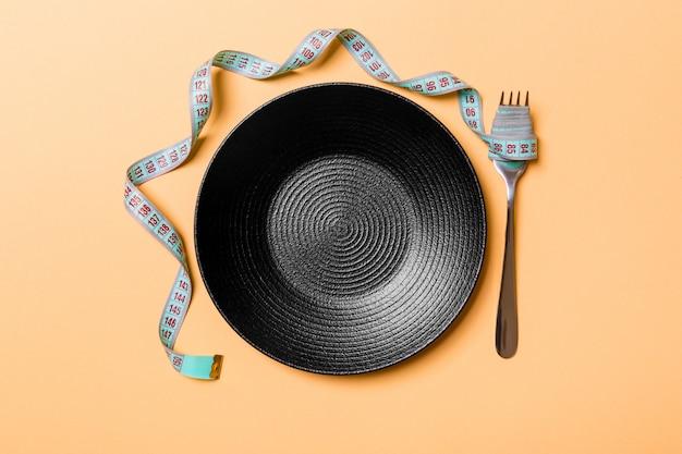 Dieta rigorosa com espaço vazio para o seu design. vista superior do prato com garfo na fita métrica em fundo laranja