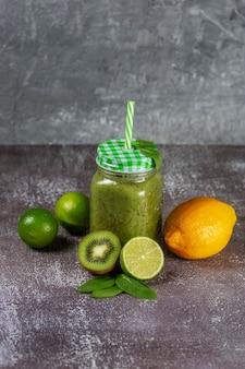 Dieta saudável suco de fruta fresca bebida com espinafre em uma jarra de vidro com um canudo sobre um fundo cinza de concreto rodeado por frutas e vegetais verdes.