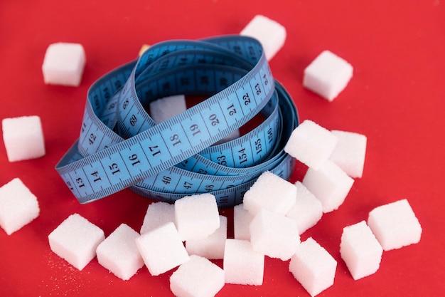 Dieta sem açúcar para perda de peso. uma pilha de cubos de açúcar branco e uma fita métrica azul nela. fundo vermelho. copie o espaço.