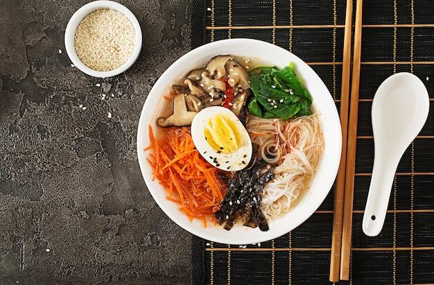 Dieta tigela vegetariana de sopa de macarrão de cogumelos shiitake, cenoura e ovos cozidos. comida japonesa vista do topo. configuração plana