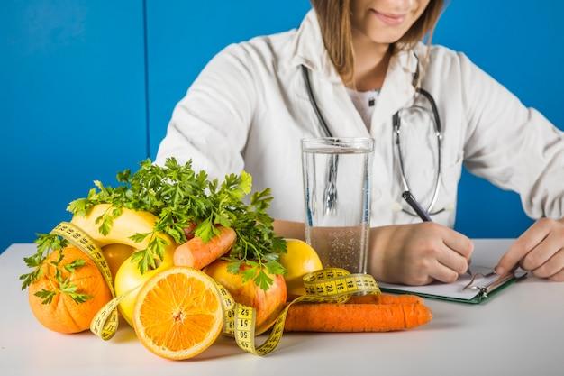 Dietista feminina, escrevendo na área de transferência com frutas frescas na mesa