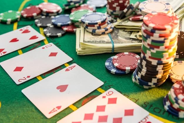 Diferente sobre fichas de pôquer de custo com cartas de jogar e dólares americanos na mesa do cassino greent. jogatina
