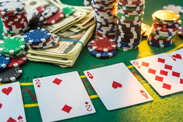 Diferente sobre fichas de pôquer de custo com cartas de jogar e dólares americanos na mesa do cassino greent
