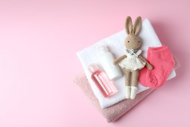 Diferentes acessórios de higiene infantil em fundo rosa