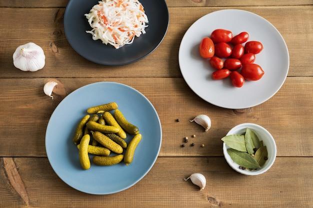 Diferentes alimentos fermentados, chucrute, pepinos e tomates marinados em pratos planos sobre fundo de madeira