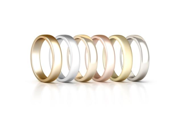 Diferentes anéis de metais preciosos definidos permanecem isolados, dourado, prata, rosa