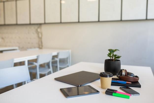 Diferentes artigos de papelaria de escritório dispostos em uma mesa branca em um escritório colaborativo
