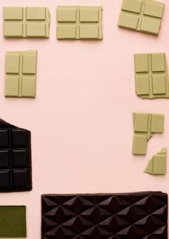 Diferentes barras de chocolate em um fundo rosa. vista de cima