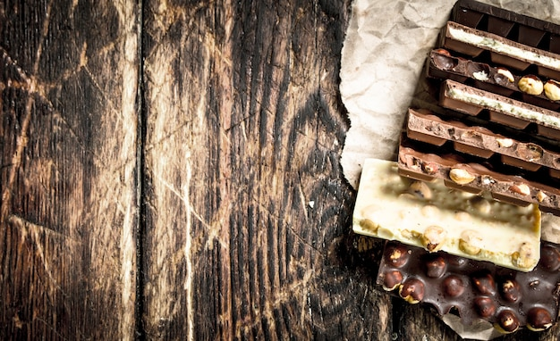 Diferentes barras de chocolate na mesa de madeira.