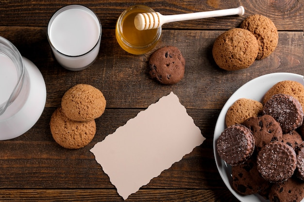 Diferentes biscoitos saborosos com mel e leite em uma mesa de madeira marrom. vista de cima