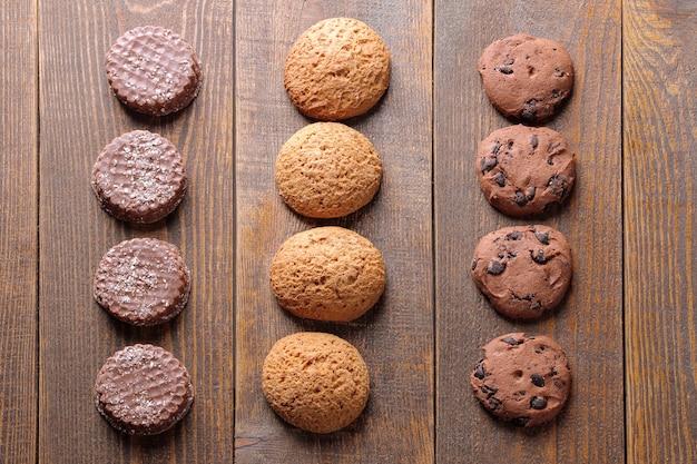 Diferentes biscoitos saborosos empilhados em uma fileira sobre uma mesa de madeira marrom. vista de cima