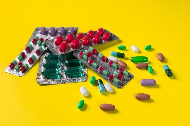 Diferentes bolhas com vários comprimidos e cápsulas e comprimidos espalhados nas proximidades, deitado sobre uma parede amarela.