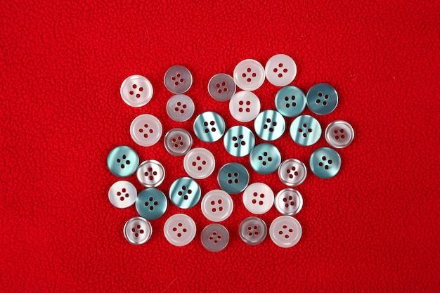 Diferentes botões de madrepérola em um pano vermelho