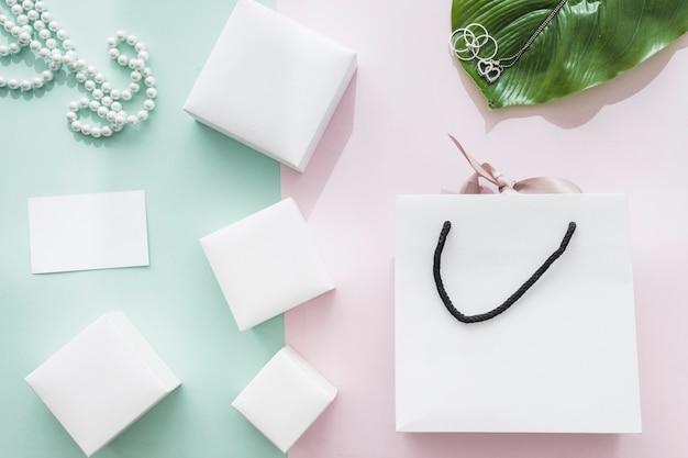 Diferentes caixas brancas com saco de compras em fundo rosa e verde