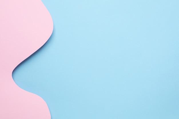 Diferentes camadas de papel abstrato e ondas azuis em rosa pastel