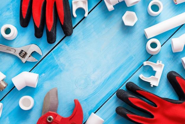 Diferentes cantos, adaptadores e acoplamentos juntamente com luvas e um cortador de tubos para tubos de plástico.