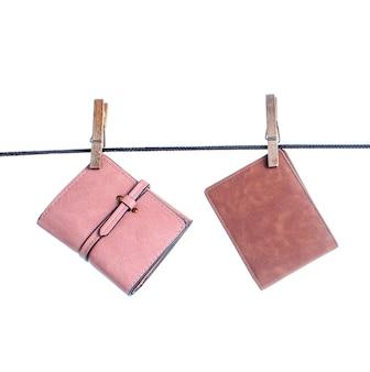 Diferentes carteiras de couro estão penduradas no varal com as fivelas isoladas