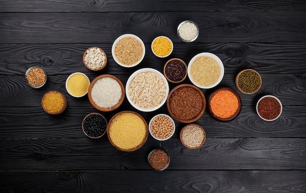 Diferentes cereais, grãos, sementes, sêmolas, leguminosas e feijões em tigelas, vista superior da coleção de mingau cru em fundo preto de madeira com espaço de cópia