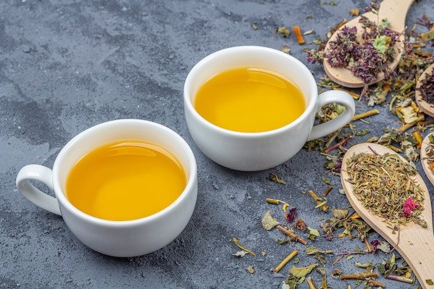 Diferentes chás secos na linha de colheres de pau e xícaras de chá