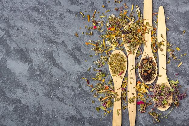 Diferentes chás secos na linha de colheres de pau