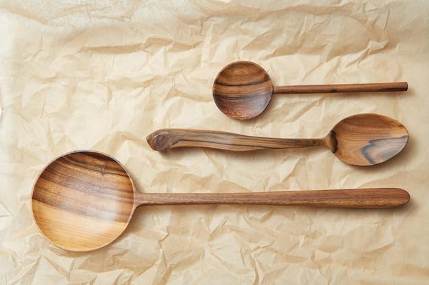 Diferentes colheres de madeira como uma moldura em papel manteiga