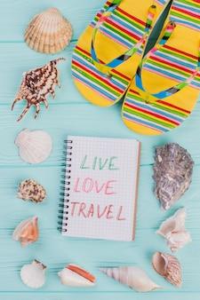 Diferentes conchas do mar e sandálias amarelas no canto sobre fundo turquesa. amo viagens ao vivo escritas no bloco de notas.
