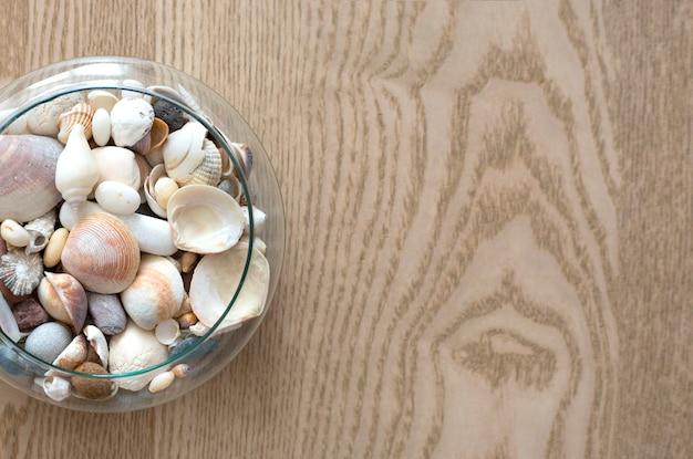Diferentes conchas do oceano em um vaso de vidro na vista superior do plano de fundo de madeira