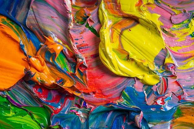 Diferentes cores brilhantes de tintas a óleo são misturadas em um close da paleta.