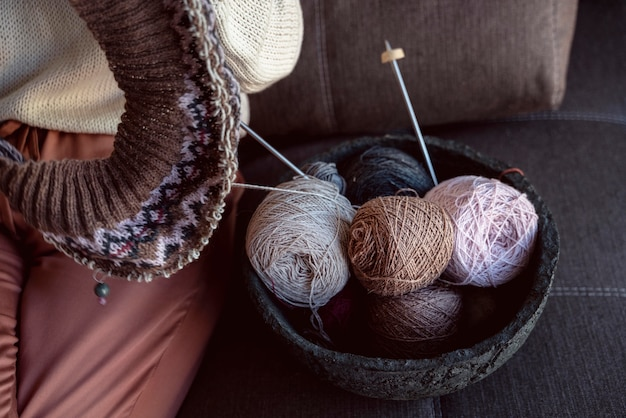 Diferentes cores de fios e acessórios de costura em uma cesta