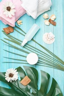 Diferentes cremes e frascos com folhas de palmeira, layout em cima da mesa