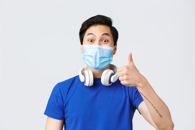 Diferentes emoções, estilo de vida e lazer durante o coronavírus, conceito covid-19. close-up de cara asiático otimista na máscara médica mostra o polegar em aprovação de uma nova música incrível tocando em fones de ouvido.