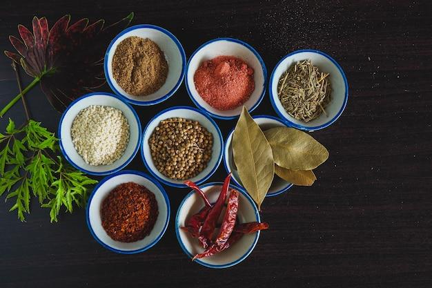 Diferentes especiarias e ervas em uma tigela pequena para cozinhar comida tailandesa no fundo.