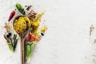 Diferentes especiarias Ingredientes alimentícios Colher de madeira no fundo do WhiteTable