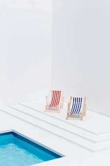 Diferentes espreguiçadeiras ao lado da piscina