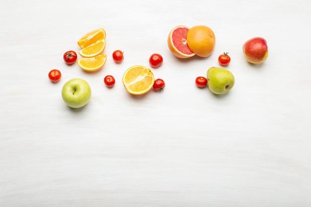 Diferentes fatias de frutas de laranja em peras e maçãs encontram-se perto de tomates vermelhos em uma mesa branca com espaço de cópia. conceito de comida vegana. espaço de publicidade