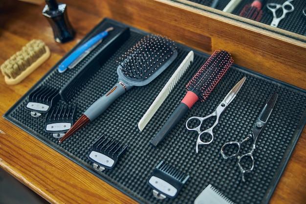 Diferentes ferramentas de tratamento de cabelo dispostas sobre uma superfície limpa em uma barbearia