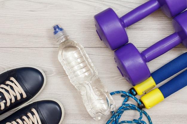 Diferentes ferramentas para fitness com garrafa de água no quarto ou academia em piso cinza