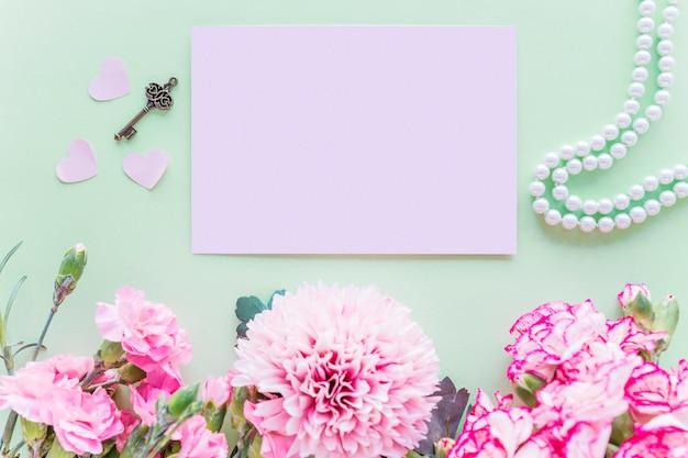 Diferentes flores cor de rosa com papel na mesa verde