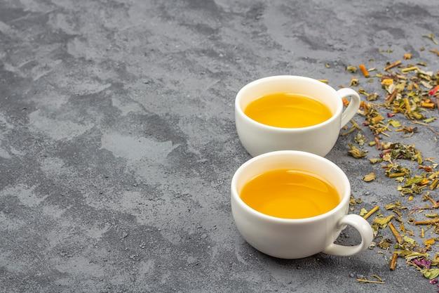 Diferentes folhas de chá secas e duas xícaras de chá verde
