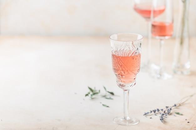 Diferentes formas de copos de vinho rosé sobre fundo claro.