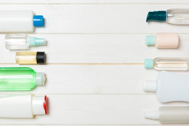 Diferentes frascos de cosméticos e recipiente para cosméticos em fundo branco de madeira