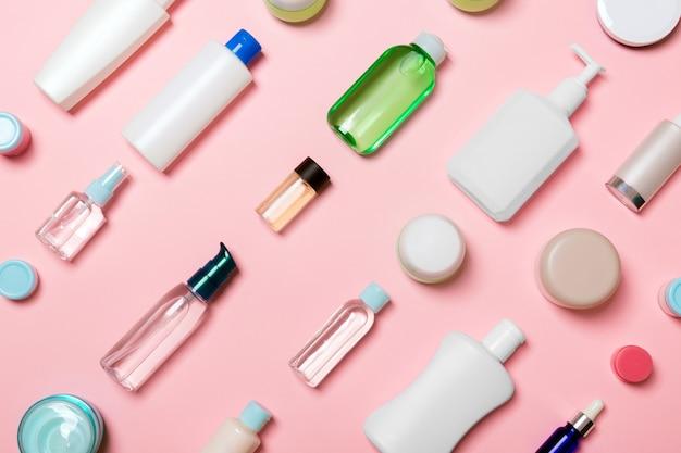 Diferentes frascos de cosméticos e recipiente para cosméticos em rosa