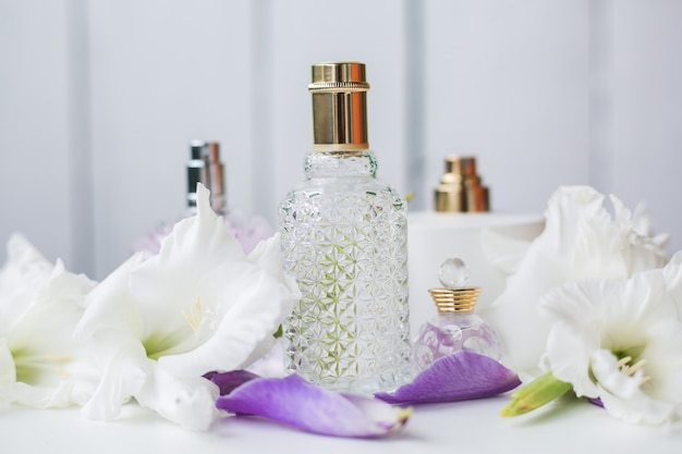 Diferentes frascos de perfume com flores brancas