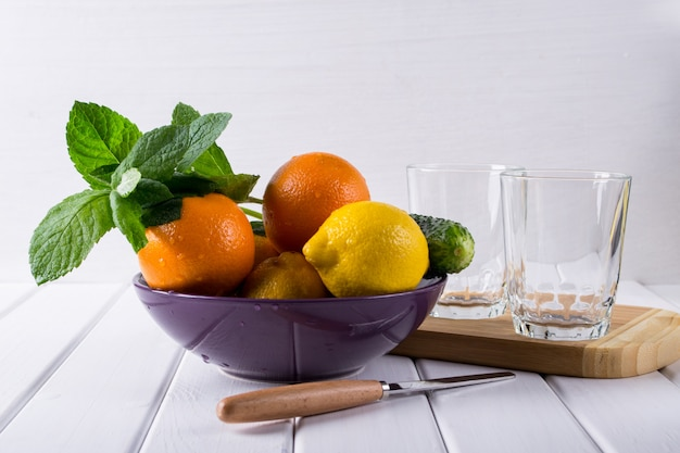 Diferentes frutas cítricas refrescantes em um prato. ingredientes de coquetel. conjunto de frutas. na mesa de madeira branca