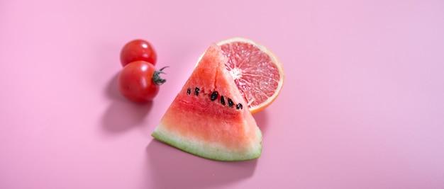 Diferentes frutas e vegetais em uma parede colorida.