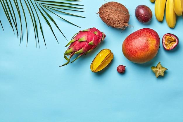 Diferentes frutas exóticas e folhas de palmeira isoladas