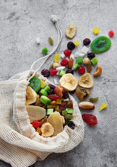 Diferentes frutas secas e nozes em um saco ecológico em uma superfície de concreto cinza