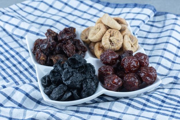 Diferentes frutas secas em uma tigela, no pano de prato, na mesa de mármore.